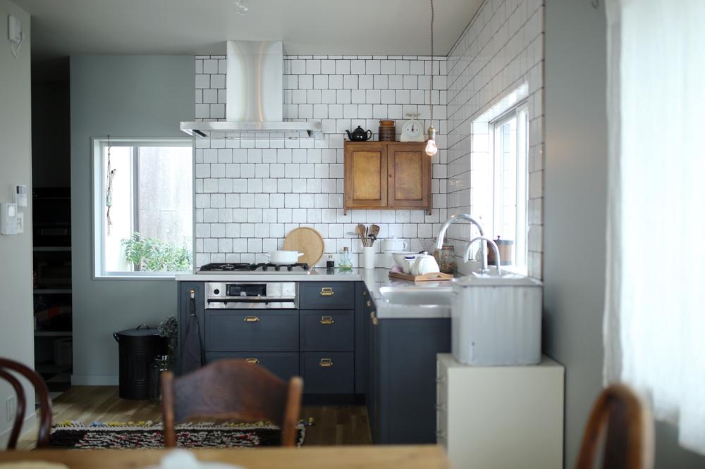明るい自然光とナイトブルーのキャビネットが印象的なキッチン。